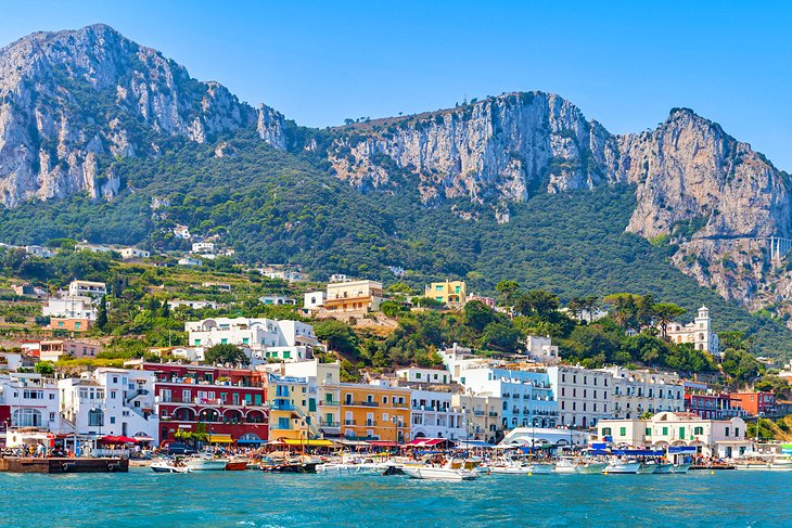 Colorful and sunny sea-side town in Italy, nestled against the edge of the ocean's sun-pierced turqoise waters.